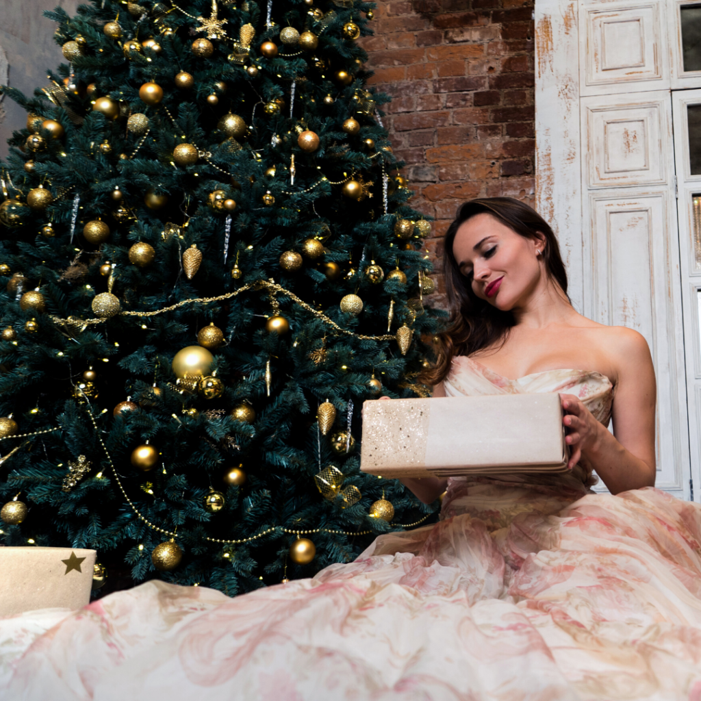 A beautifully dresses girl in front of a Christmas tree