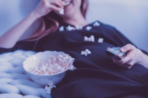 girl spending time during quarantine by laughing and eating popcorn while holding a tv remote