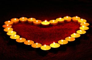 candles put beside each other in a way that reminds of a heart