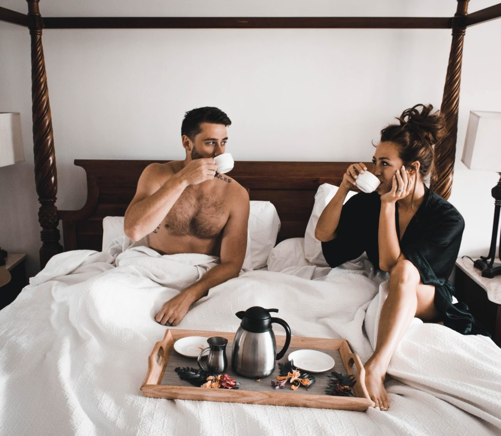 couple celebrating sugar daddy's day by having breakfast in bed