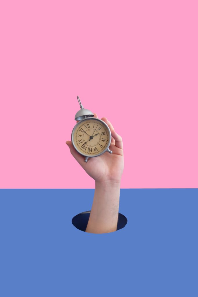 hand holding clock to remind of the importance of timing when making a video call