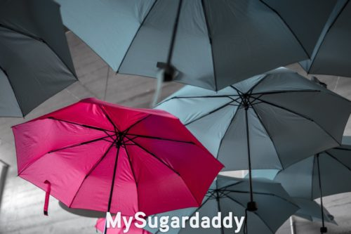 pink umbrella stands out from grey ones representing successful sugar babies