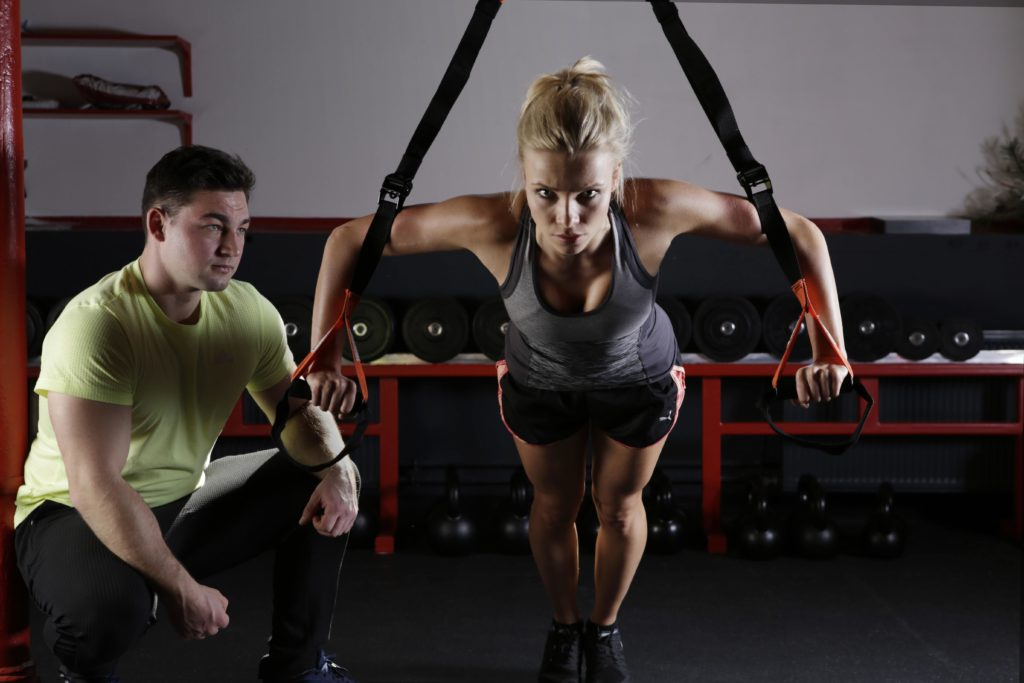 woman exercising under supervision of a male personal trainer
