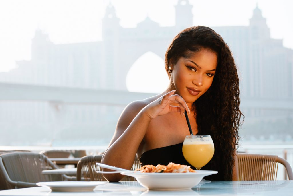 example of an ideal profile picture: woman having lunch with a touristic attraction in the background