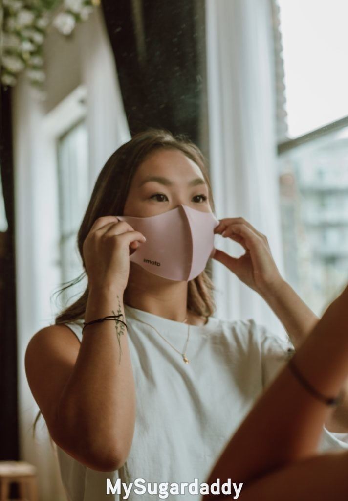 woman putting mask on and practicing social distancing